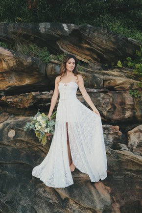 The Johanna Wedding Dress on rocks with flowers front lifestyle