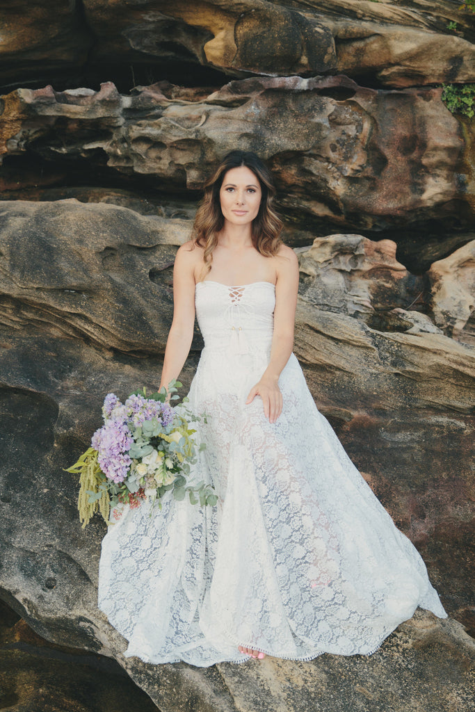The Johanna Wedding Dress full shot front on with bride on rocks with flowers