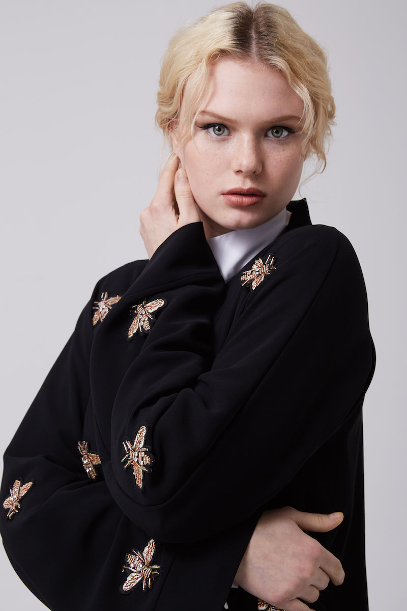 FERADJE modest black abaya with gold bee patches made from crepe close up view