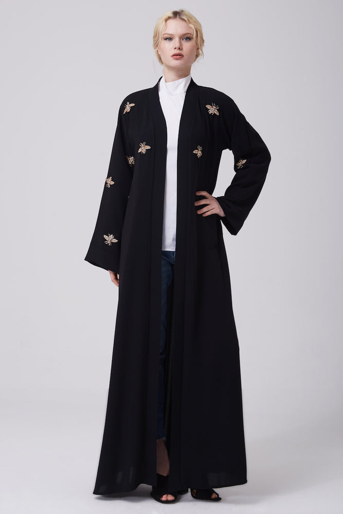 FERADJE modest black abaya with gold bee patches made from crepe full length view