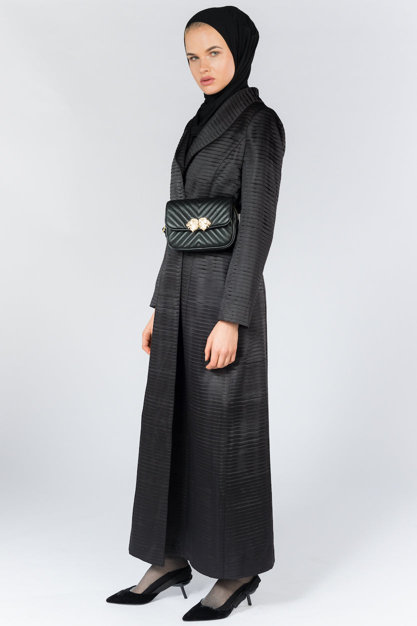 FERADJE Modest Women Royal Abaya in black with collar and elegant pleated abraham fabric. It is unbuttoned and has fitted straight arms. It is design as a coat so it's perfect for any occasion and season. It can be machine washed side view