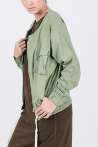 Muzca Imogen Linen Jacket In Green Modest Loose Collarless Jacket with Zipper, Chest Pockets, and Drawstring in Linen