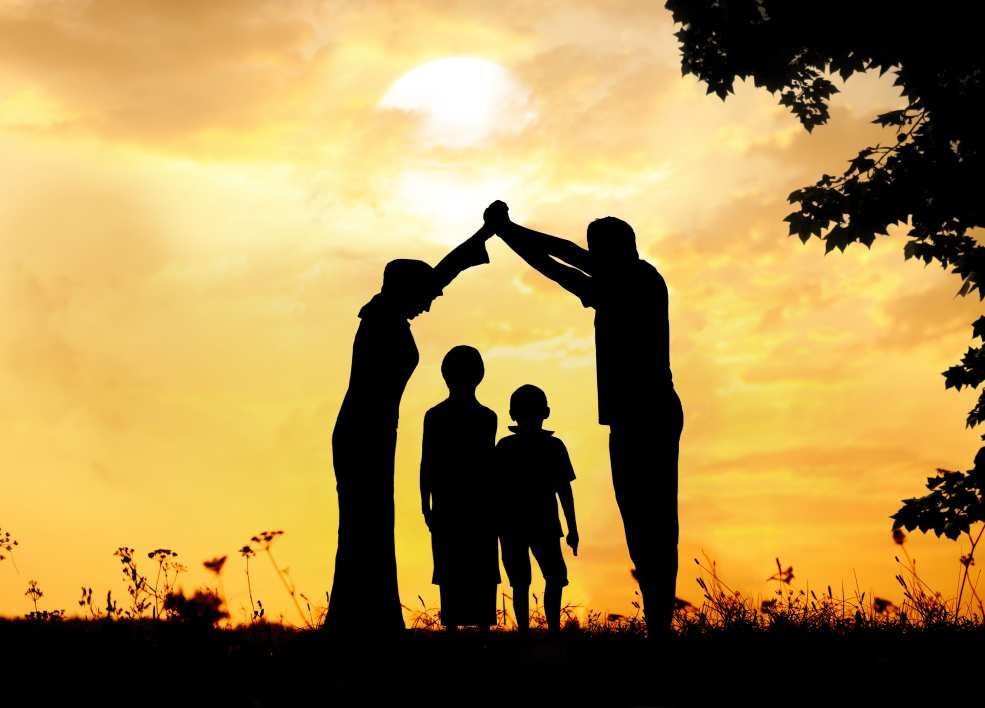 A silhouette of a mother and father standing over their two children forming a roof of house with their arms and hands during a sunset