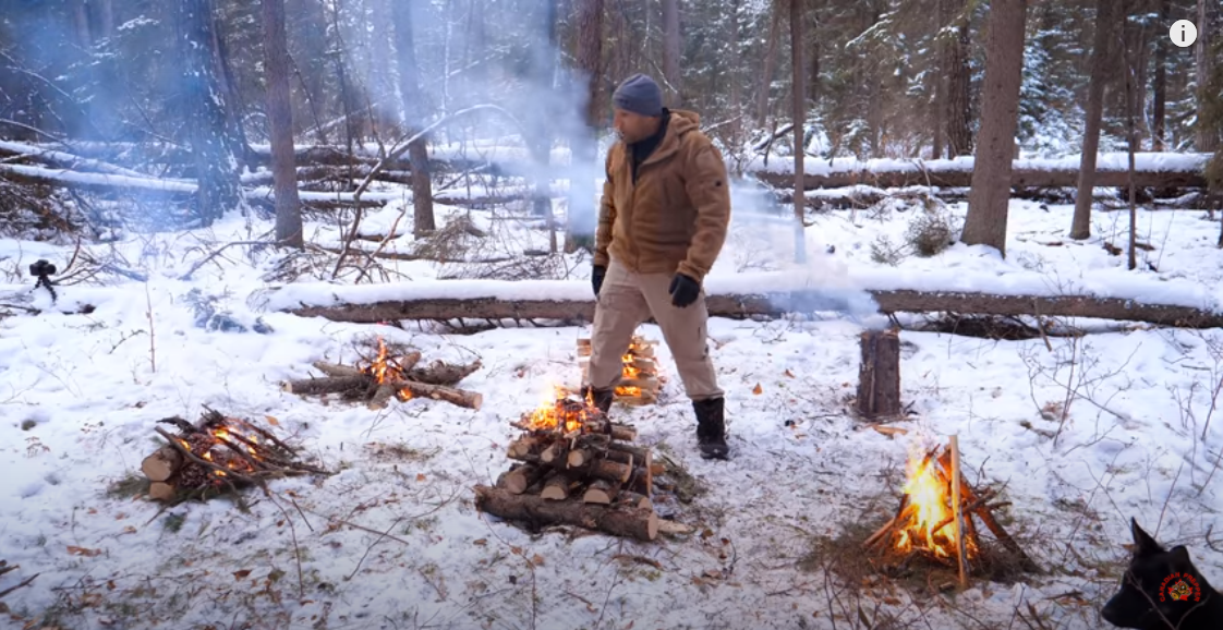 Canadian prepper standing in between the six different types of fire builds: tipi, lean to, torch, cabin, top down and star build