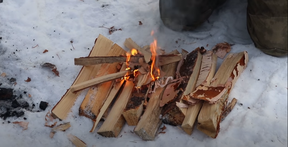 Building a fire from kindle and wood shavings on the snowy ground