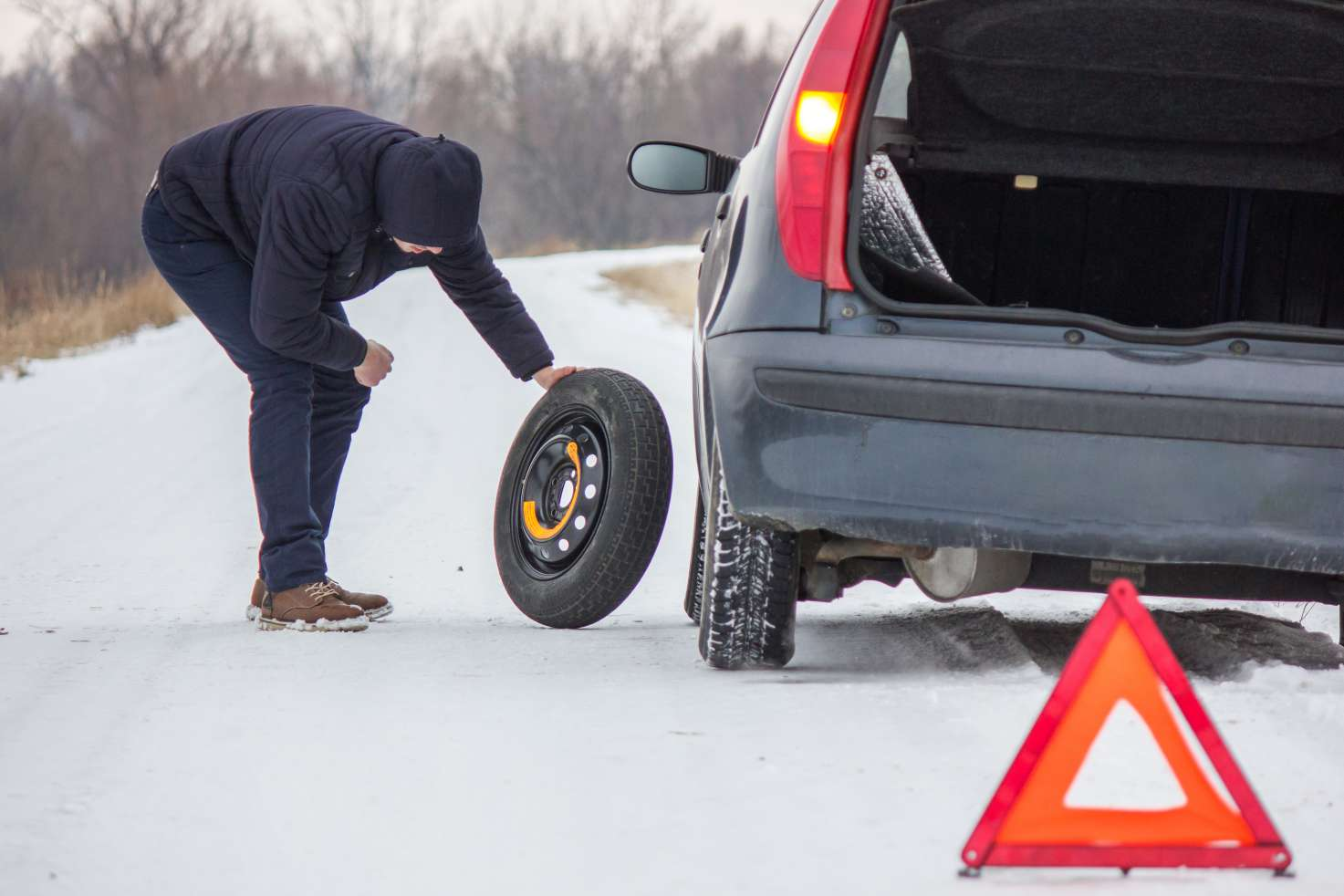 Man changing a tire on his car in the winter. A pylon is set up for passing cars.
