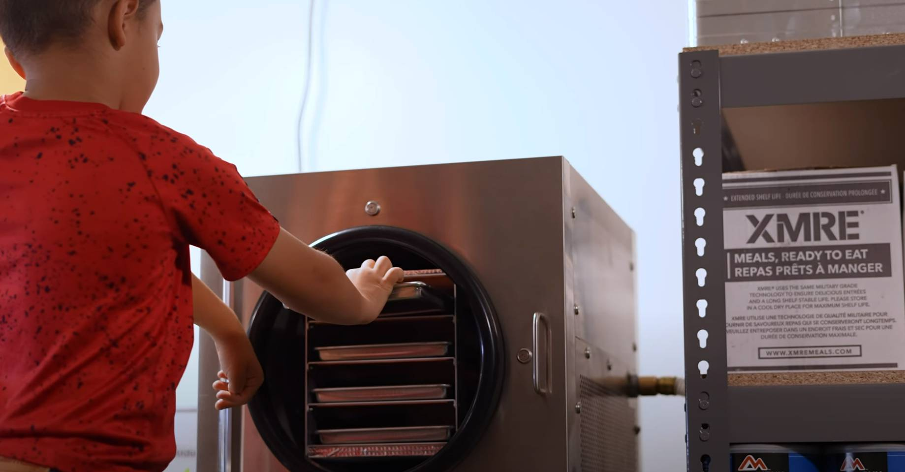 Son placing a tray of food into a freeze dryer
