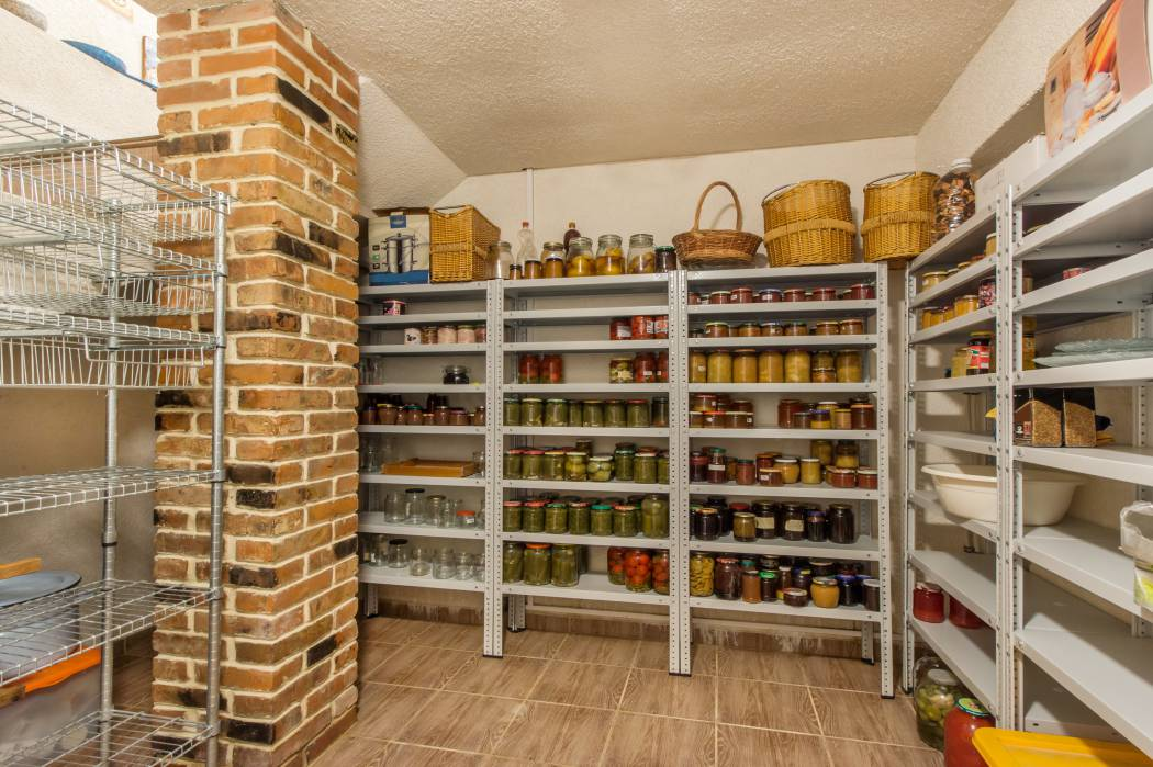 A basement cold room with storage full of food and household goods