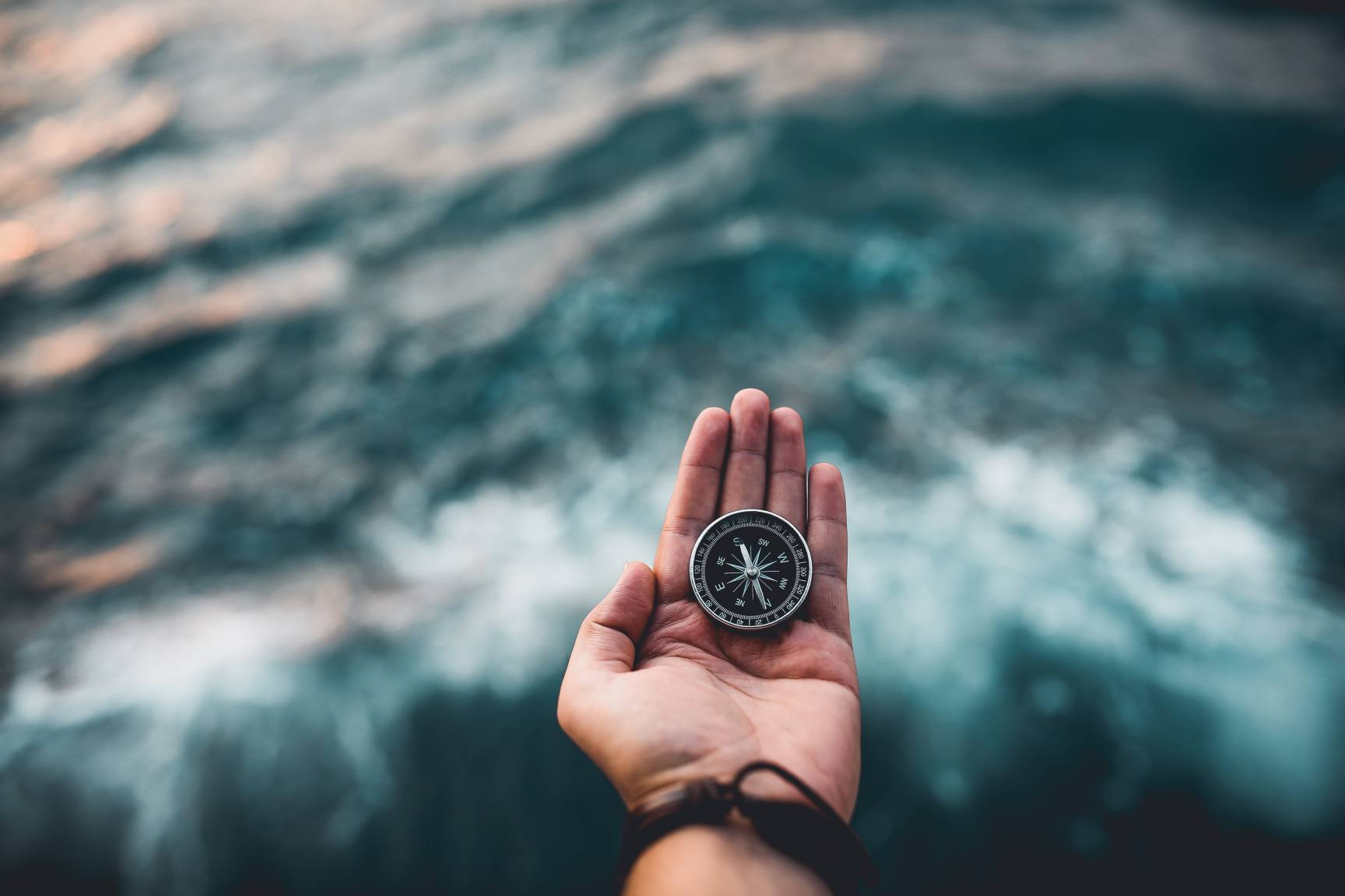 Man holding a compass in front of an ocean tide
