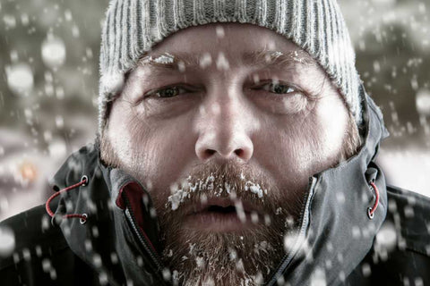 A bearded man wearing a grey toque fighting the cold showing signs of hypothermia