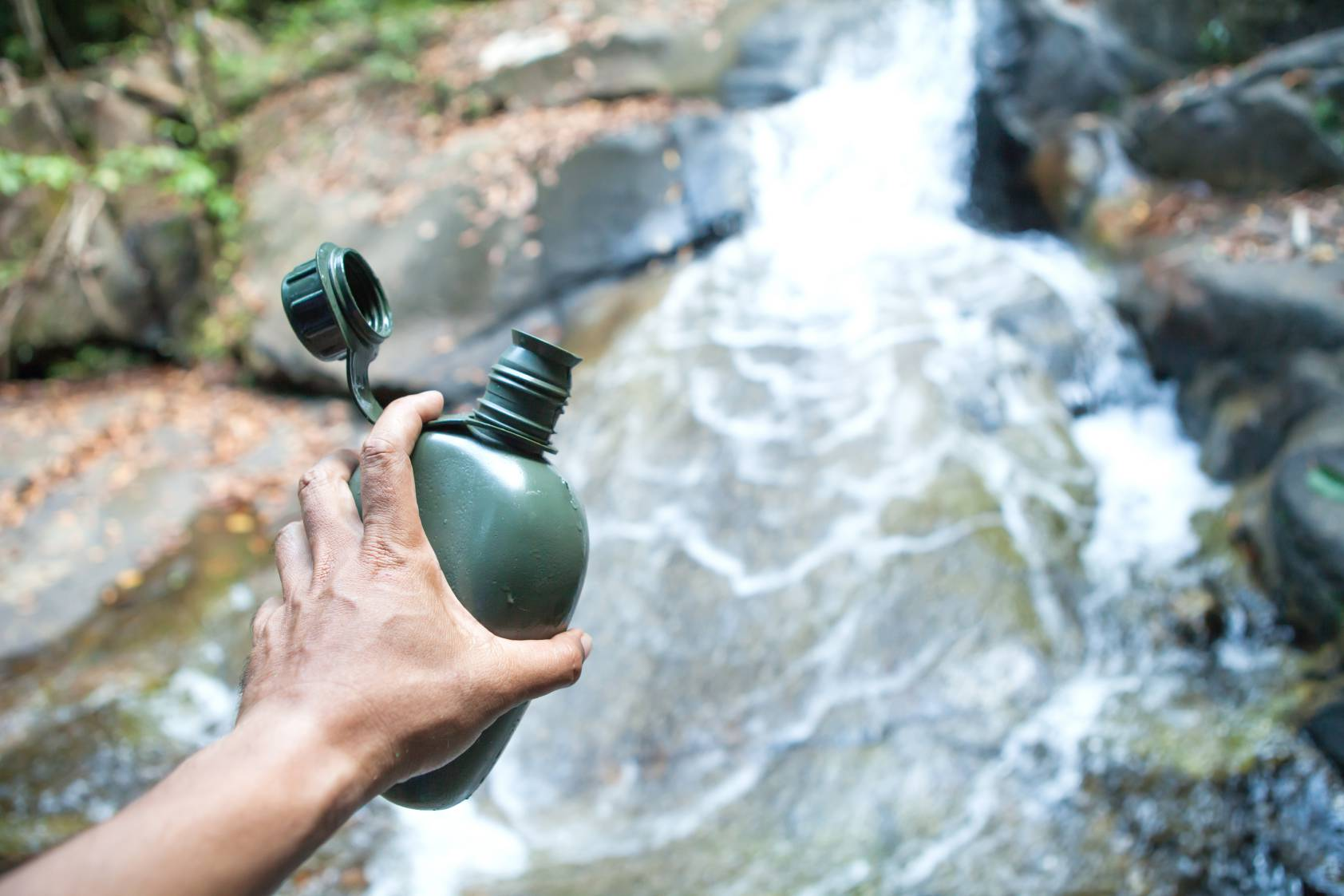 A man looking to fill up his green coloured canteen in a flowing stream of river water