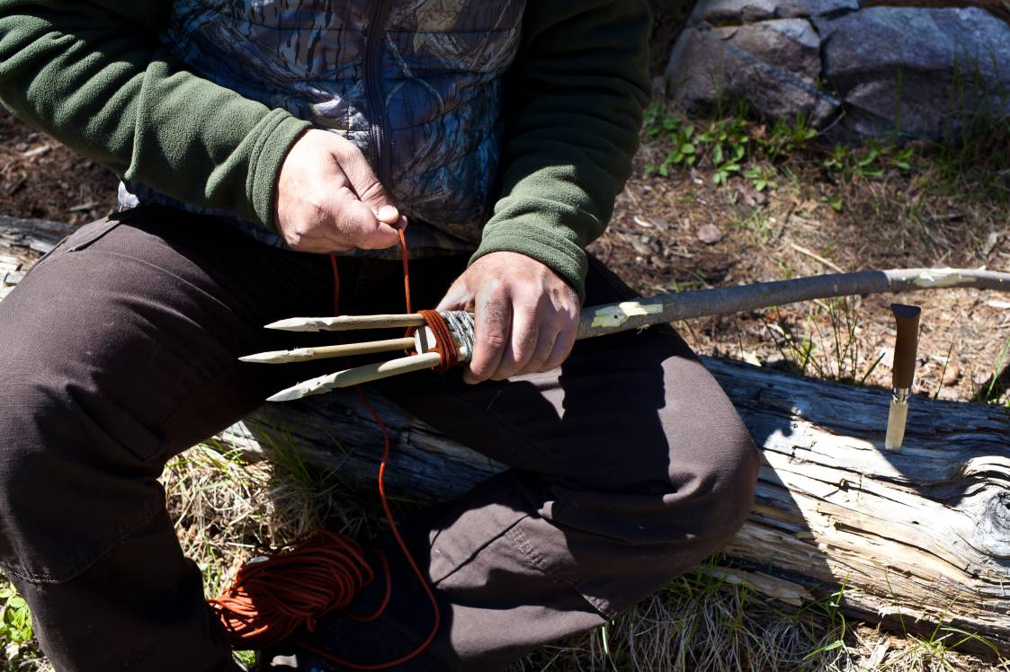 Man making a fishing spear with a utility knife