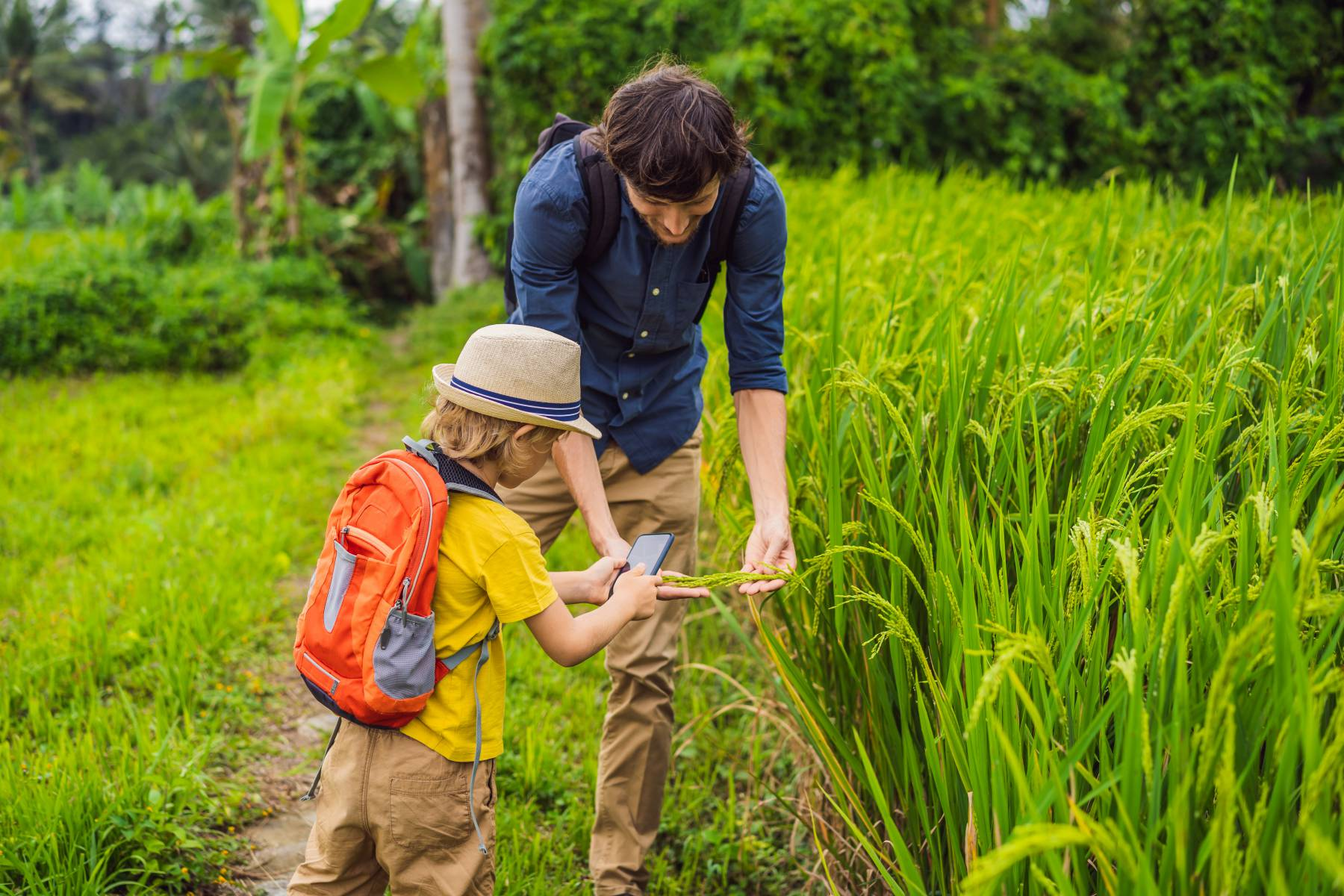 Man in navy blue shirt showing child in yellow shirt with a sun hat how to forage