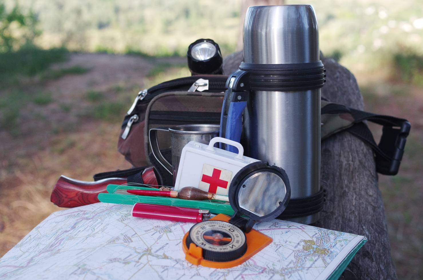 A compass, thermos, medical kit, flashlight, and knife on top of a map in the woods.