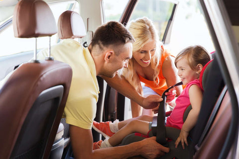 A Mother wearing a white shirt and purse and a Father wearing a yellow polo shirt buckling their infant child into a car seat