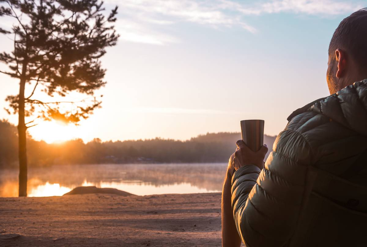 Man drinking a coffee from a thermos watching the sunrise over a lake