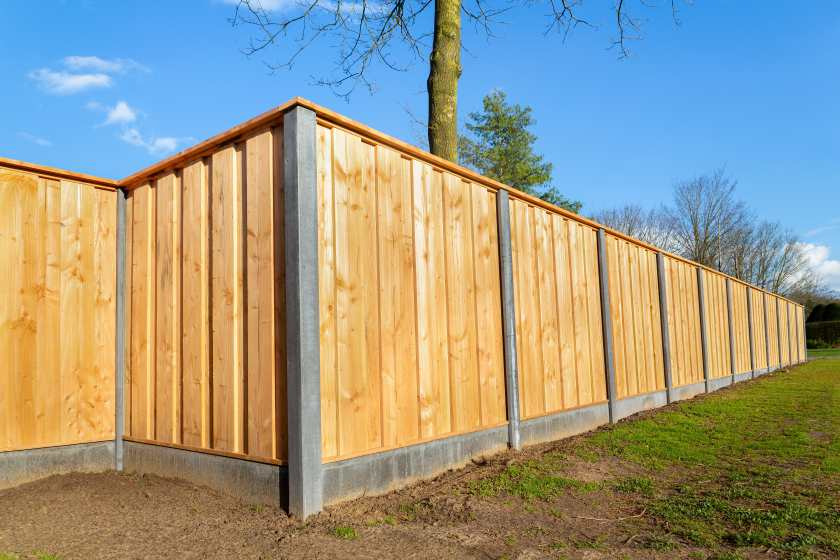 Tall fence to keep intruders out, surrounding a home during the summer.