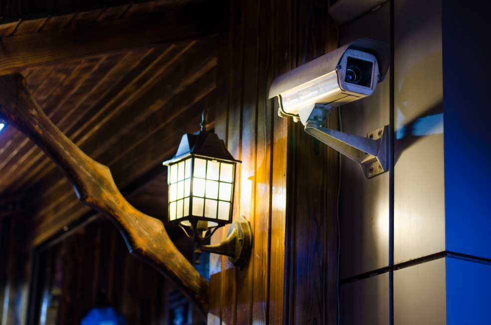Night-time home surveillance camera beside a lantern on the side of a house.