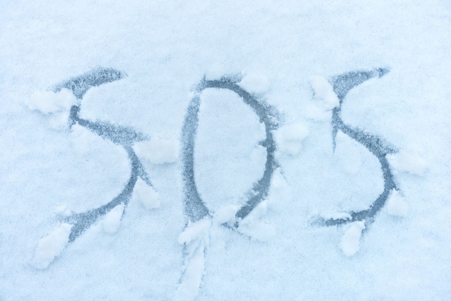SOS - call for help signal written in the snow
