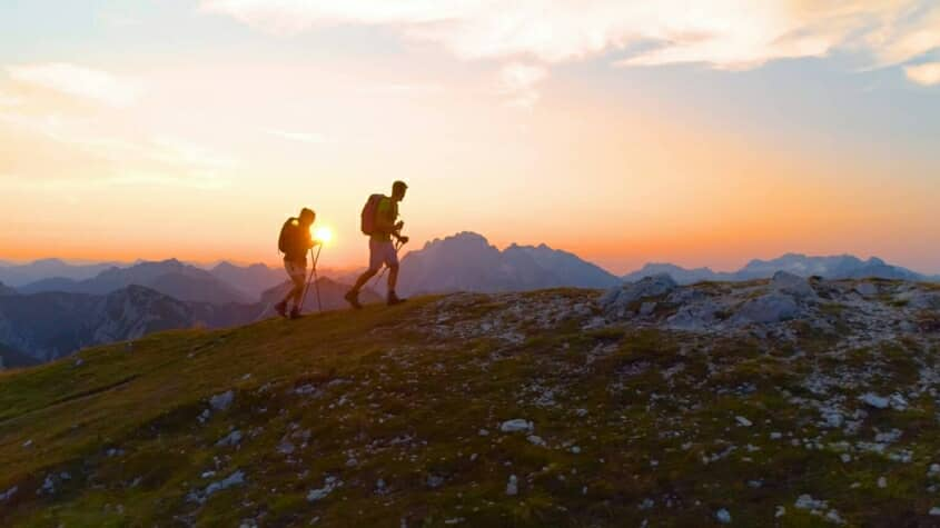 Two people trekking in the sunset