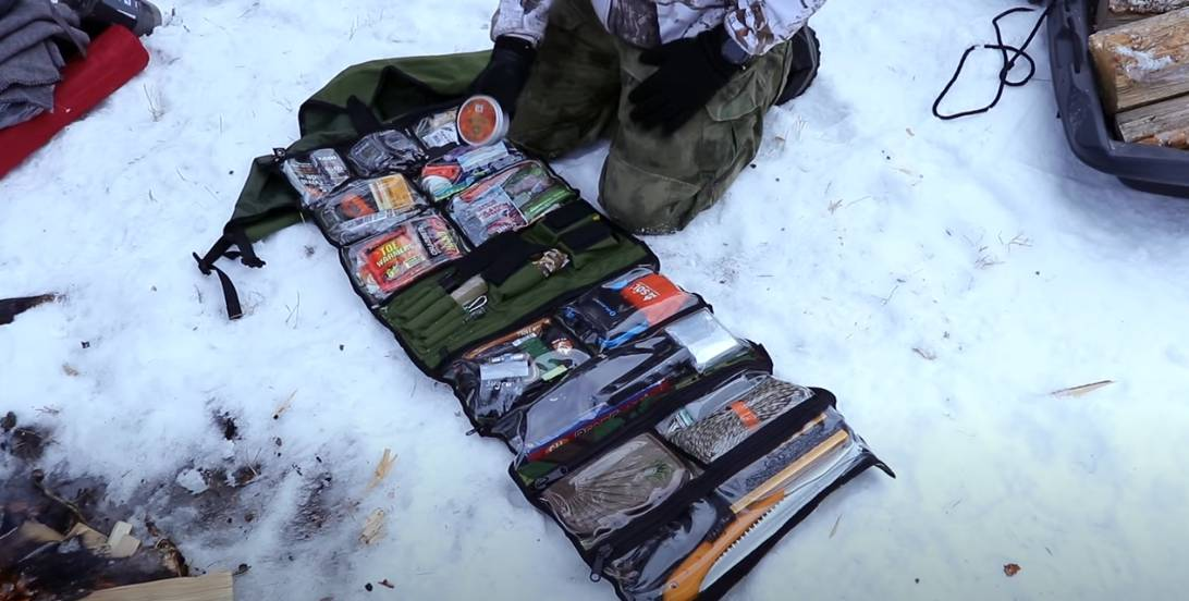 Winter bug out roll with various gear like: fat rope sticks, paracord, freeze dried food and other prepper gear