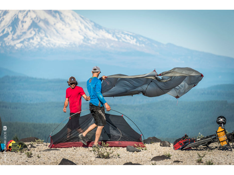 2 guys setting up the MSR Carbon Reflex Ultralight Tent. A man wearing a blue shirt is placing the weather cover over the tent while another man wearing a red shirt helps. Two bicycles are shown on the ground and a large mountain in the background.