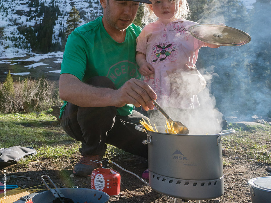 A father in a kelly green shirt turns spaghetti pasta in a Large WindBurner Stock pot while his blonde haired daughter wearing a pink dress holding the pot lid. Steam rises from the pot as they cook the pasta together on a camp stove. A snow covered hill is in the background.