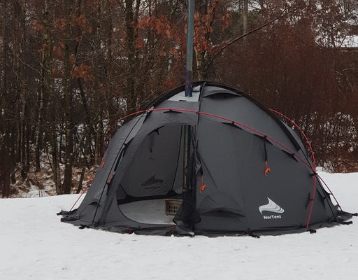 Nortent Gamme 4 Winter Hot Tent in black with red tent poles. The tent is set up outside in the snow amongst a group of trees.