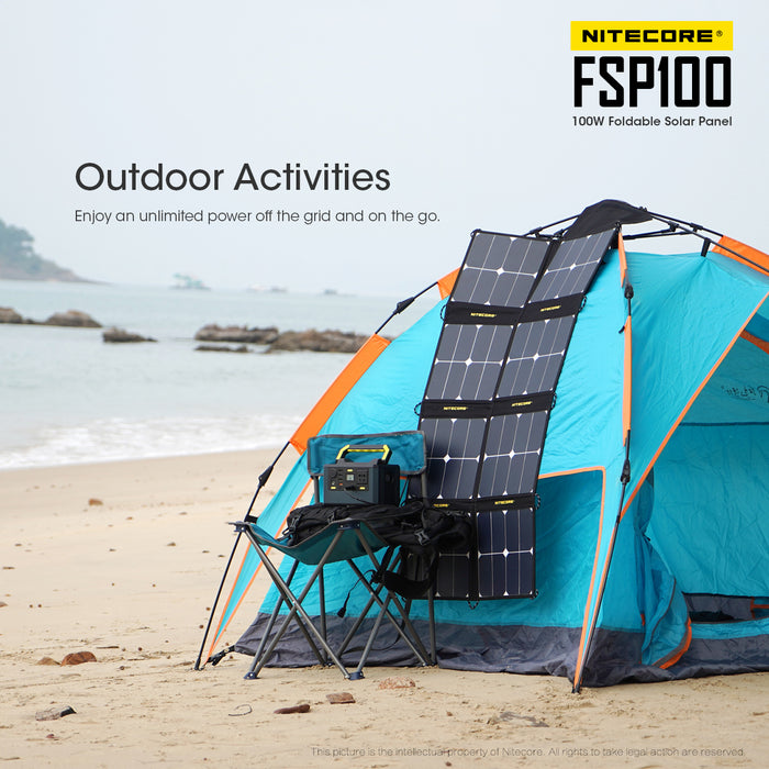 A Nitecore FSP100 100 Watt foldable solar panel laid on a blue tent on a beach charging a power bank on a camping chair via usb. The ocean tide rolls in the background.