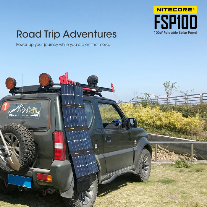 A Nitecore FSP100 flold out solar panel on the side of a forest green suv.