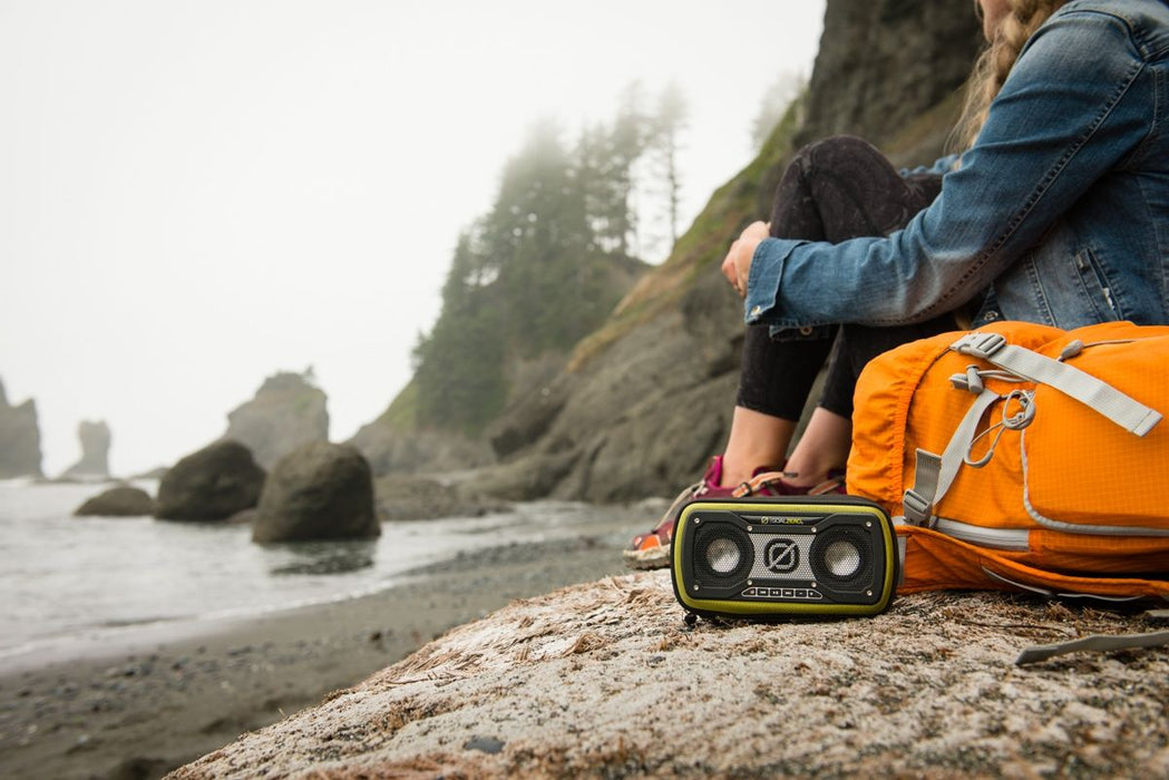 A girl relaxing and looking out on the beach during a foggy day with her orange hiking backpack and Goal zero Rock out 2 Speaker.