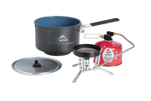 MSR WindBurner Group Stove System, with the black coloured cermaic cooking pot that nests inside the camping stove to be secure during wind and bad weather. The red ISOPRO propane tank is connected to the camp stove and the pot lid is laid beside.