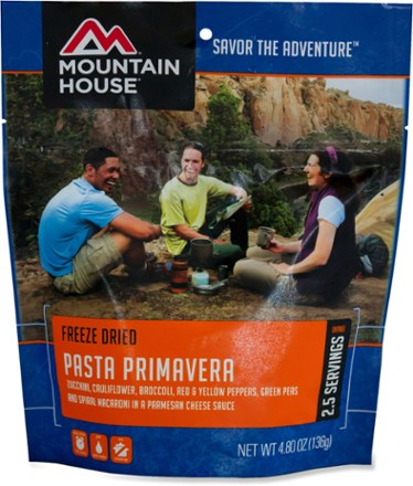 Three people sitting around a camp stove, preparing a meal of Freeze Dried Pasta Primavera from Mountain House. In the background is a canyon face and a beige coloured tent.