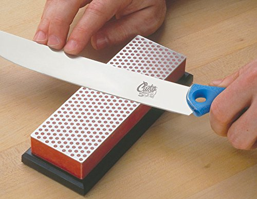A person using two hands to sharpen a Cuda 500 knife on a DMT Diamond Sharpener Block.