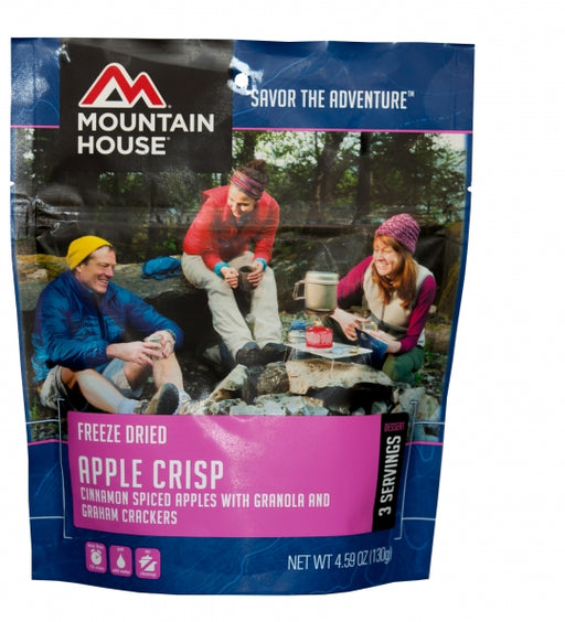 Mountain House Apple Crisp Freeze Dried Package. On the package is 3 campers sitting around a fire eating the apple crisp laughing and smiling.