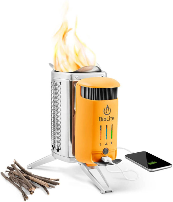 The BioLite CampStove 2 burning a fire in the canister with a pile of sticks to the left and a mobile device to the right being charged via usb through Patented combustion technology.