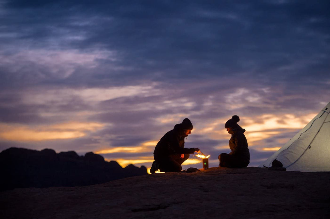 A couple sitting around a fire made by BioLite CampStove 2 at sunset outside of their tent.