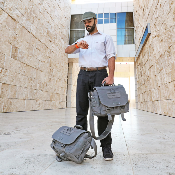Traveler with two Gray Vanquest ENVOY-17 (Gen-4) Messenger Bags checking the time and awaiting a pickup to the airport outside a large marble stone building.