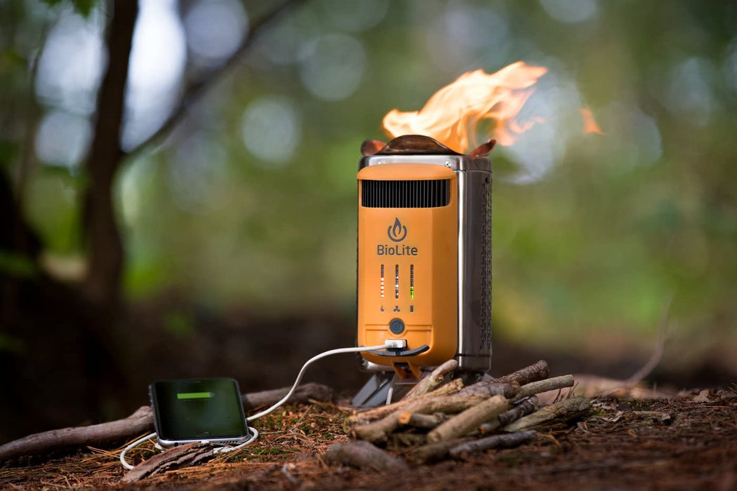 The BioLite CampStove 2 outside laid standing up on the ground outdoors with bundles of sticks surrounding it and charging a mobile device via white usb cable. On the campstove are lit up indicators of the different energy sources.