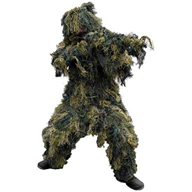 Person wearing the Bushline Outdoors Guillie Suit with balck boots and a concealed rifle on a white background.