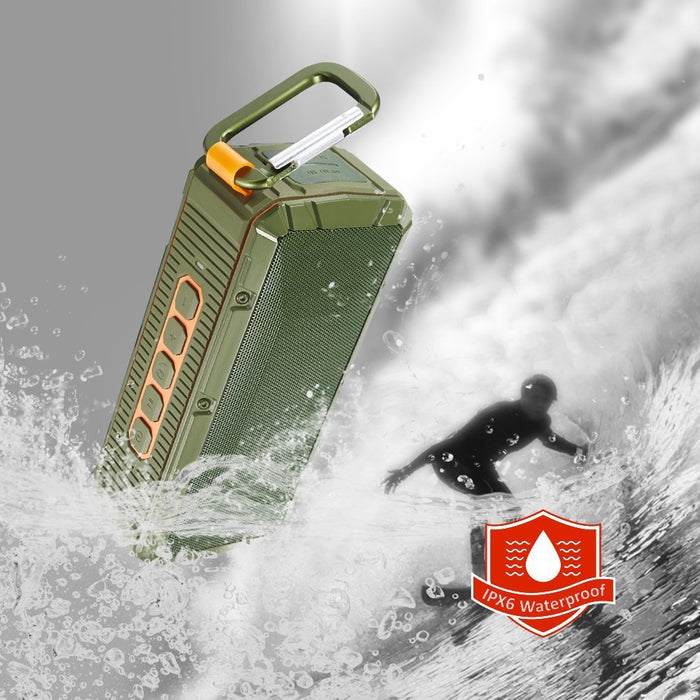 Kaito V3 Ruggedized IPX6 waterproof speaker with a surfer in the background, waves and water splash the speaker.