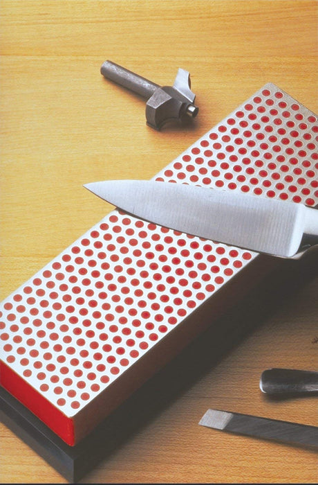 A knife being sharpened across the DMT Diamond Course Grit Sharpener. The dot pattern is of a red colouring on a black base.