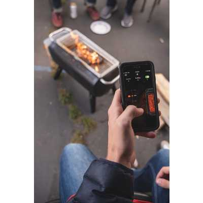 Person using the BIolite FirePit app to manage the flame height output. People sitting around in chairs on pavement observing.