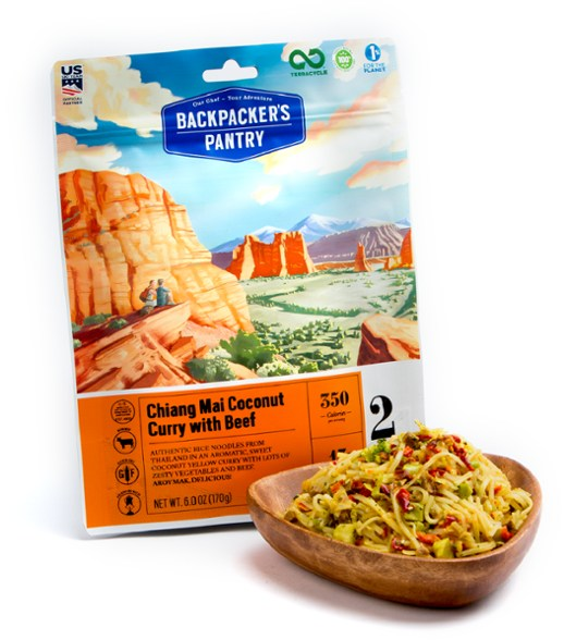 Freeze dried package of backpackers pantry chiang mai coconut curry with beef, along side a wooden bowl of the prepared meal