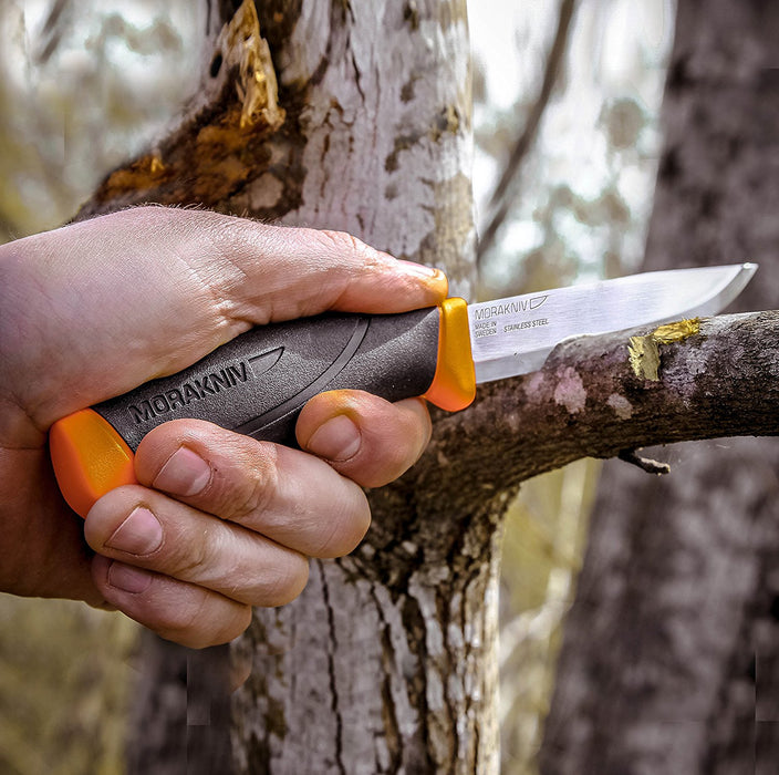 A man holding the Morakniv Companion Knife in orange and black cutting through a tree branch in the woods.