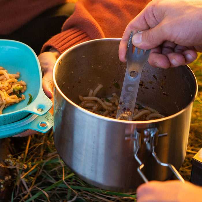 A person scooping noodles out of a camping pot with a UCO titanium spork. A person wearing an orange sweater holds a blue bowl next to the pot.