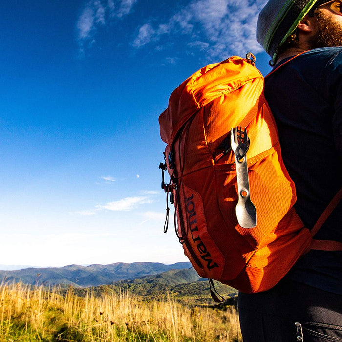 A UCO titanium spork hooked to an orange marmot backpack. A hiker wears the pack with spork walking through a field of tall grass. Rolling green hills and blue sky populate the background.