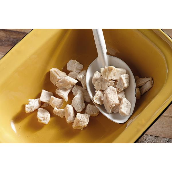 A white camping spoon scooping out freeze dried chicken bits from a mustard coloured bowl. In the background is a dark hardwood floor.