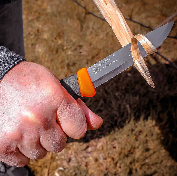 A Companion ranger knife being used to strip wood from a branch for fire kindling.