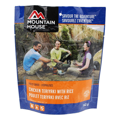 Mountain House Chicken Teriyaki freeze dried food package in blue with an image of three campers sitting around outside a yellow tent enjoying the meal. A canyon and trees populate the background.